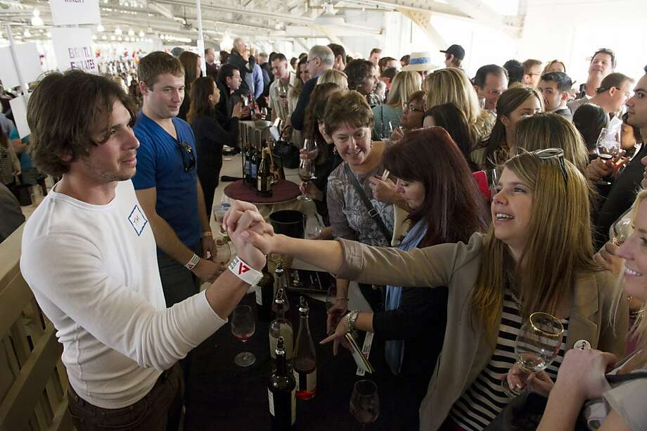 "Ben Flajnik co-owner of Envolve Winery and star of  the TV show ""the Bachelor"" greets Brooke Barnecut during the San Francisco Chronicle Wine Competition, Saturday February 18, 2012 in San Francisco, Calif. Photo: David Paul Morris, Special To The Chronicle"