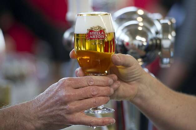 A volunteer hands over a glass of Stella Artois beer during the San Francisco Chronicle Wine Competition, Saturday February 18, 2012 in San Francisco, Calif. Photo: David Paul Morris, Special To The Chronicle