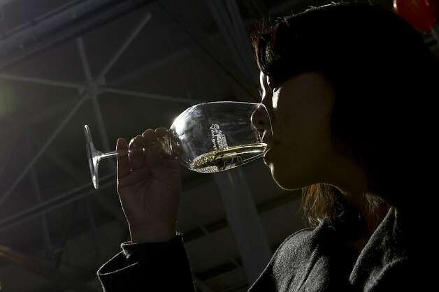 Jennifer (no last name given) gets a new pour of wine as Cathy Kim, left, inspects her glass during the San Francisco Chronicle Wine Competition, Saturday February 18, 2012 in San Francisco, Calif. Photo: David Paul Morris, Special To The Chronicle
