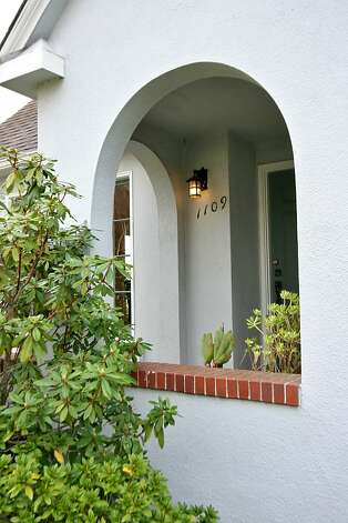 Entry Arches greet visitors to the home's front entrance. Built in the English country cottage style, this home, built in 1924, provides four bedrooms and two baths across 2,431 square feet. It is on the market for $829,000. Photo: Liz Rusby