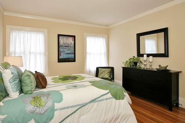 One of the four bedrooms. This home, nestled in the quaint Crocker Highlands neighborhood, exemplifies the English country cottage archetype. Built in 1924, its light blue stucco exterior and clipped-gable roofline are classic details of the style, while inside the house modern upgrades integrate seamlessly with the vintage charm. Photo: Liz Rusby