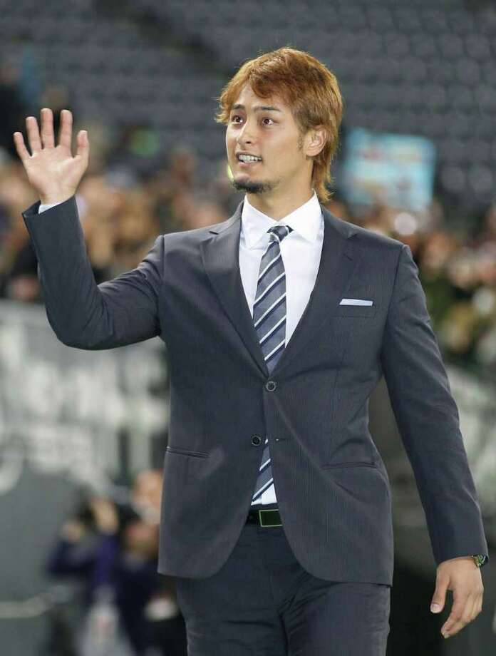 Japanese pitcher Yu Darvish, who'll play for the Texas Rangers next season, waves to his Japanese fans at Sapporo Dome baseball park on Tuesday, Jan. 24, 2012. More than 10,000 fans packed the stadium to say sayonara to Darvish, who days ago formally inked a six-year, $56 million contract with the Rangers. (AP Photo/Kyodo News) JAPAN OUT, MANDATORY CREDIT, NO LICENSING IN CHINA, FRANCE, HONG KONG, JAPAN AND SOUTH KOREA Photo: AP