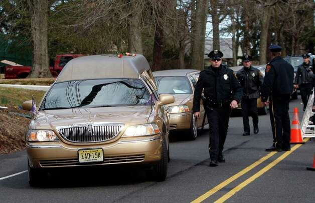 The hearse carrying the body of Whitney Houston, adorned with roses on the roof that were tossed by fans, arrives at Fairview Cemetery for her burial in Westfield, N.J., Sunday, Feb. 19, 2012. (AP Photo/Rich Schultz) Photo: Rich Schultz, ASSOCIATED PRESS / AP2012
