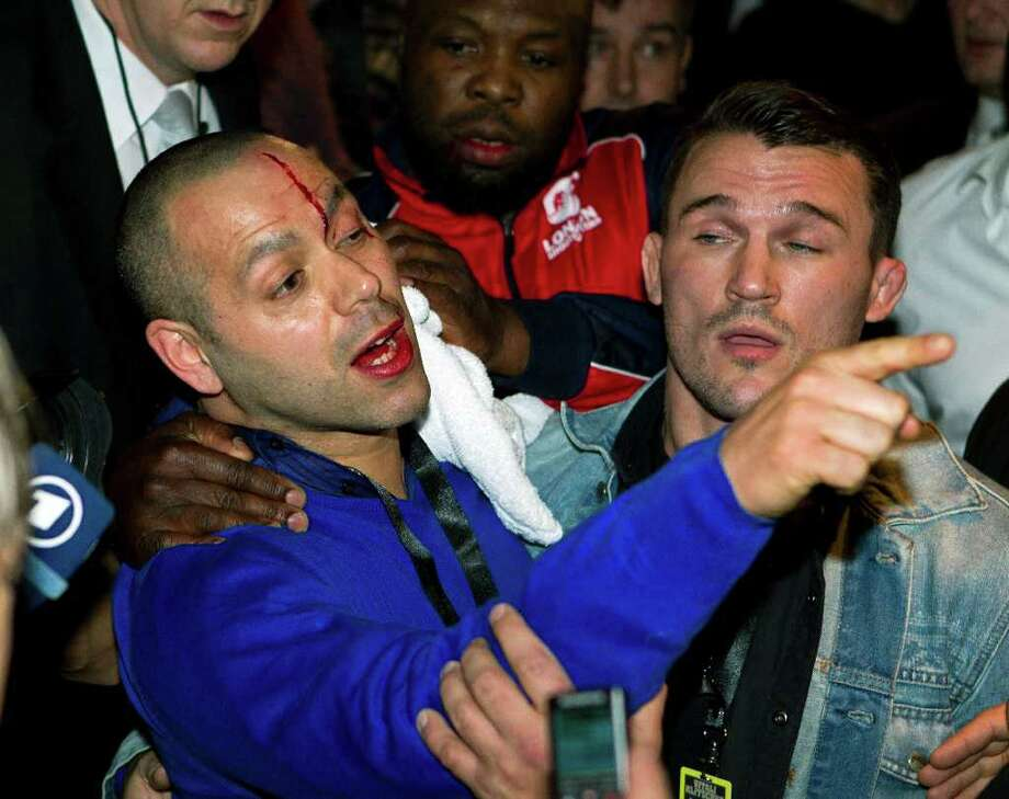 Adam Booth (left), David Haye's coach, bleeds from a head cut after the brawl between Dereck Chisora and his fighter. Photo: Marianne Mueller, AP / dapd