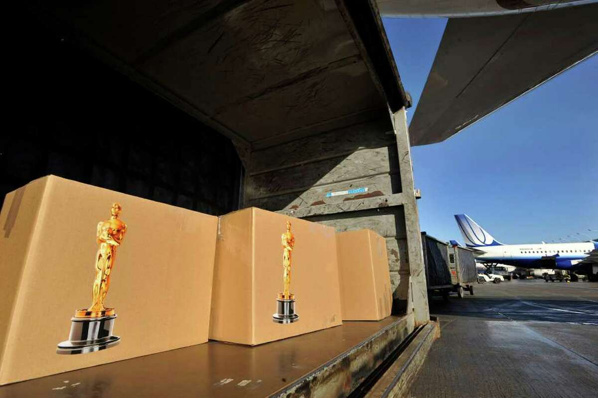 """Oscar awards wait to be loaded before the flight on """"Oscar One"""" to Los Angeles at O'Hare International Airport in Chicago Thursday, Feb. 9, 2012. The awards will be distributed at the 84th annual Academy Awards on Feb. 26 at the Kodak Theatre in the Hollywood section of Los Angeles. (AP Photo/Paul Beaty)"""