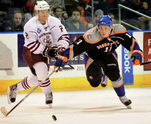 Hershey defenseman Patrick McNeill, left, hooks his stick under the arm of Sound Tiger Casey Cizikas as Cizikas pusues the puck in the offensive zone during the first period of their AHL matchup at the Webster Bank Arena in Bridgeport on Sunday, February 19, 2012. No penalty was called on the play. Photo: Brian A. Pounds / Connecticut Post