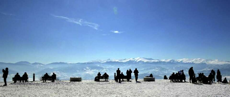 People enjoy the sun and the view at the top of Vodno Mountain above the town of Skopje, Macedonia,
