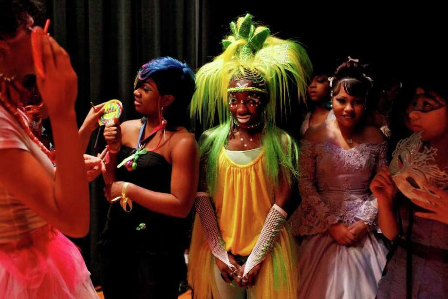 "Sam Houston High's Dajah Thomas, 15 (from left, in black dress), Marion Jackson, 17, and Lizzy Rangel, 15, and Roosevelt High's Crystal Cruz, 14, wait before taking part as models in the fantasy hair competition of the ""Adorn, Inspiration that Beautifies"" show Sunday, Feb. 19, 2012, at Sam Houston. The show aims to give cosmetology students a chance to display their creativity. Jackson, dressed as ""Queen of the Corn,"" placed second with her stylist, Tijuana Jones, in the fantasy event. Photo: Lisa Krantz, San Antonio Express-News / @2012 SAN ANTONIO EXPRESS-NEWS"