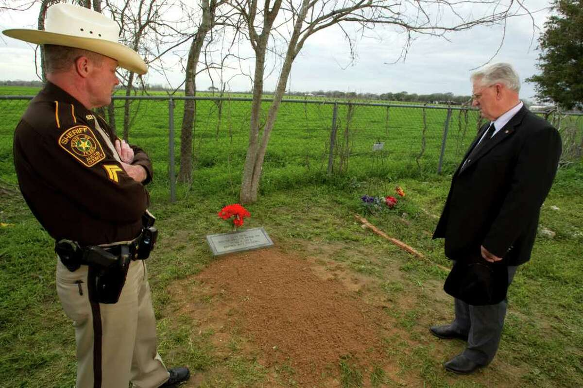 Austin County Sheriff's Deputy Cpl. Scott Minyard, left, and Dennis King, Austin County Precinct 4 Justice of the Peace, stand near the grave of recently identified Gloria Stringer Thursday, Feb. 16, 2012, in Wallis. Since 1975, the woman that occupied the grave was unknown. On February 10, after 37 years, the woman was identified as a young mother who disappeared from Texas City in 1975. Her body was found in the Brazos River on June 7, 1975 about two miles north of I-10. King has been working on the case since 1975. Minyard helped solve the mystery in identifying the woman. ( Brett Coomer / Houston Chronicle )