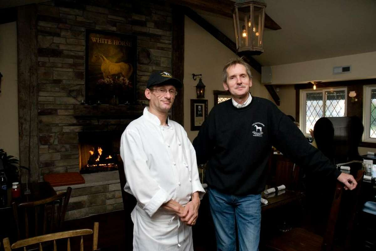 Chef Fabris Denis and owner John Harris stand in front of the fire place in The White Horse, A Country Pub & Restaurant, Thursday afternoon.