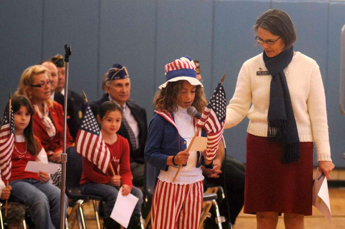 Northville Elementary School Principal Susan Murray holds the microphone for Third grader Alexandra Panetta while she talks about a relative in the military during the 11th annual Veterans Day program at the school Monday.