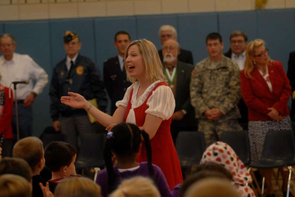 Diana Beddow leads the group in singing You're a Grand Old Flag, Monday at Northville Elementary School for the 11th Annual Veterans day program.