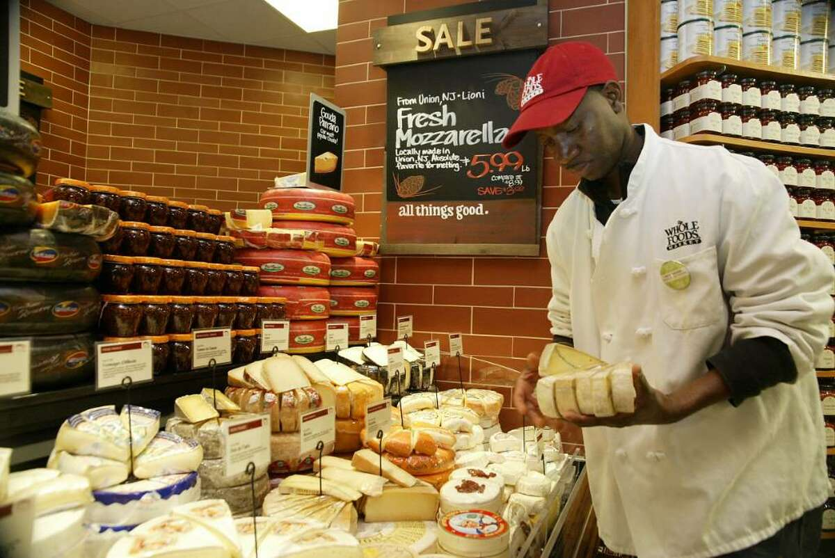 Lamin Samateh puts out imported cheeses for the wednesday opening of Whole Foods in Milford.