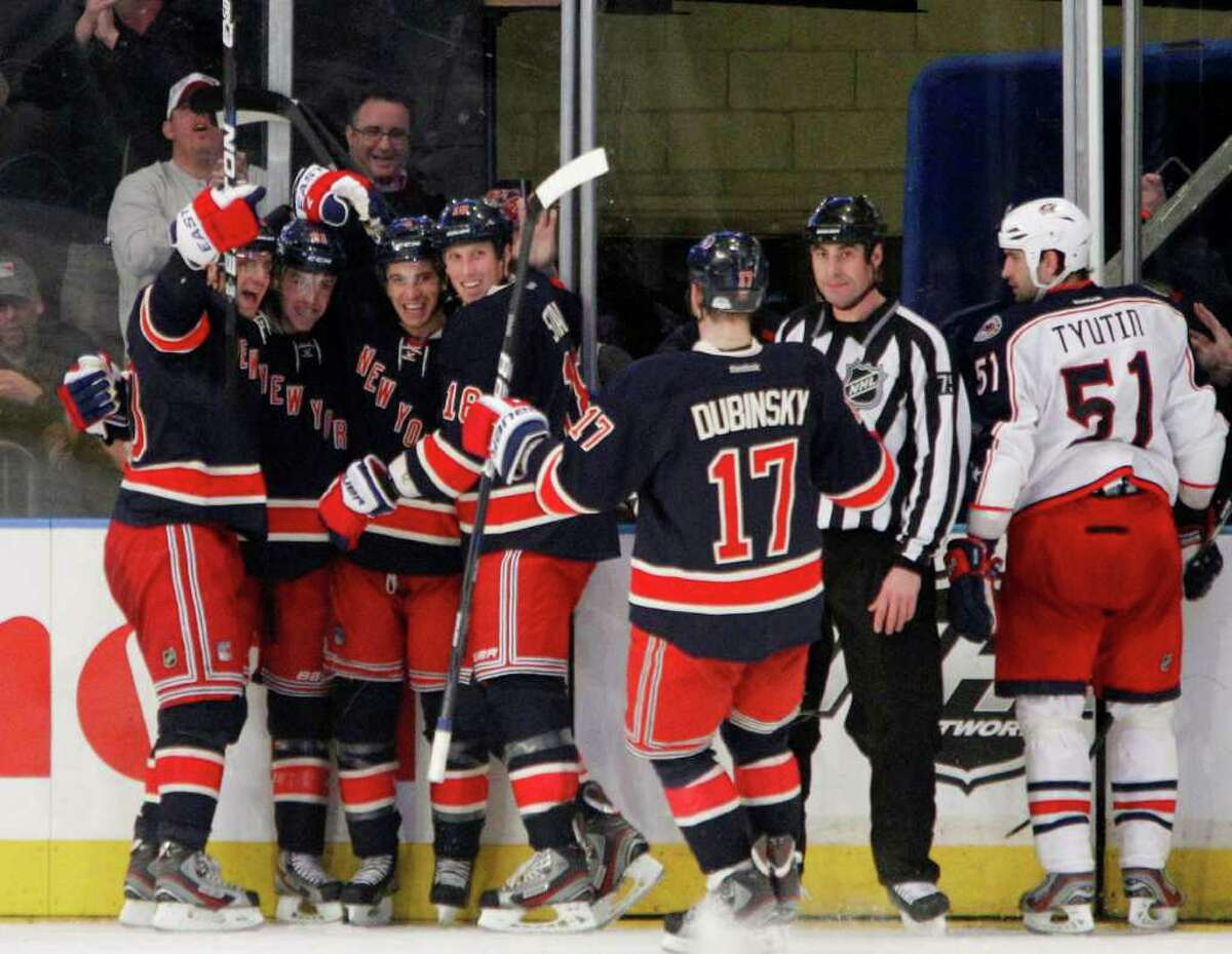 The New York Rangers celebrate Derek Stepan's goal in overtime of an NHL hockey game against the Columbus Blue Jackets at Madison Square Garden in New York, Sunday, Feb. 19, 2012. Blue Jackets defenseman Fedor Tyutin is at right. The Rangers won 3-2. (AP Photo/Kathy Willens)