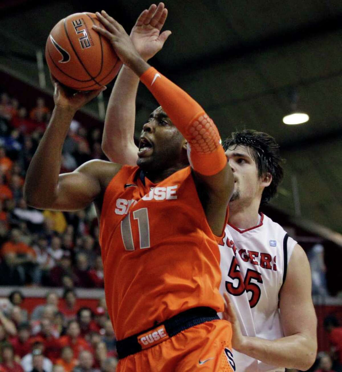 Syracuse's Scoop Jardine (11) takes a shot in front of Rutgers' Gilvydas Biruta, (55) of Lithuania, during the first half of an NCAA college basketball game in Piscataway, N.J., Sunday, Feb. 19, 2012. Syracuse won 74-64. (AP Photo/Mel Evans)