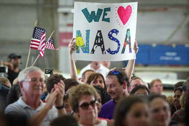 A woman holds a sign in support of NASA during a welcome home ceremony for the crew of the space shuttle Atlantis, the final mission of the NASA shuttle program, at Ellington Field in Houston on Friday, July 22, 2011. Photo: Smiley N. Pool, Houston Chronicle / © 2011  Houston Chronicle