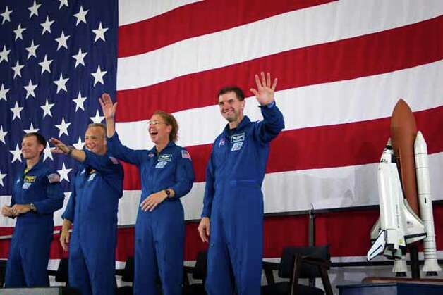 The crew of STS-135, from left, commander Chris Ferguson, pilot Doug Hurley, and mission specialists Sandy Magnus and Rex Walheim wave to the crowd during a welcome home ceremony for the crew of the space shuttle Atlantis, the final mission of the NASA shuttle program, at Ellington Field in Houston on Friday, July 22, 2011. Photo: Smiley N. Pool, Houston Chronicle / © 2011  Houston Chronicle