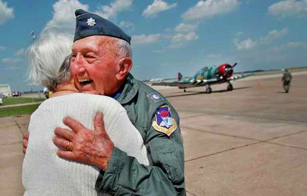 Retired Lt. Col. Ted Wolfram III embraces wife Barbara Wolfman after landing the AT-6 Texan, the same plane he used to fly while in the Air force back in 1944, at Ellington Field  on Saturday, Sept. 24, 2011, in Houston. Photo: Mayra Beltran, Houston Chronicle / © 2011 Houston Chronicle
