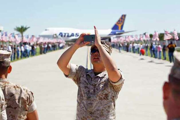 Sgt. Khanh Hoang takes a photo of the crowd as the plane containing 337 Marines from the Houston-based 1st Battalion, 23rd Marine Regiment returns home to Ellington Field and to cheers from an estimated 1000 people after a seven-month combat tour in Afghanistan, Saturday, Oct. 1, 2011, in Houston. Photo: Michael Paulsen, Houston Chronicle / © 2011 Houston Chronicle