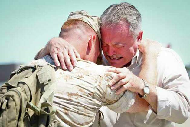 First Lieutenant Chris Huff (left) consoles Jerry Smith, father of Staff Sgt. Jeremy Smith, 26, who was killed in a friendly fire incident in Afghanistan in April, after the the arrival of the Houston-based 1st Battalion, 23rd Marine Regiment to Ellington Field returning from a seven-month combat tour in Afghanistan, Saturday, Oct. 1, 2011, in Houston.   Three-hundred and thirty-seven Marines returned home to Houston to cheers from an estimated 1000 people. Photo: Michael Paulsen, Houston Chronicle / © 2011 Houston Chronicle