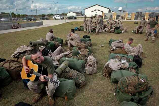 "Marine Lance Corporal Justin Black plays his guitar before boarding a bus at the Armed Forces Reserve Center at Ellington Field and engaging in pre-deployment training at Camp Pendleton in California Tuesday, Nov. 9, 2010, in Houston.   Marines assigned to the 1st Battalion, 23rd Marine Regiment, 4th Marine Division, also known as the ""The Lone Star Battalion"", leave for pre-deployment training at Camp Pendleton in California.  The group will then deploy early next year in support of the II Marine Expeditionary Force in southwestern Afghanistan. Photo: Michael Paulsen, Houston Chronicle / Houston Chronicle"