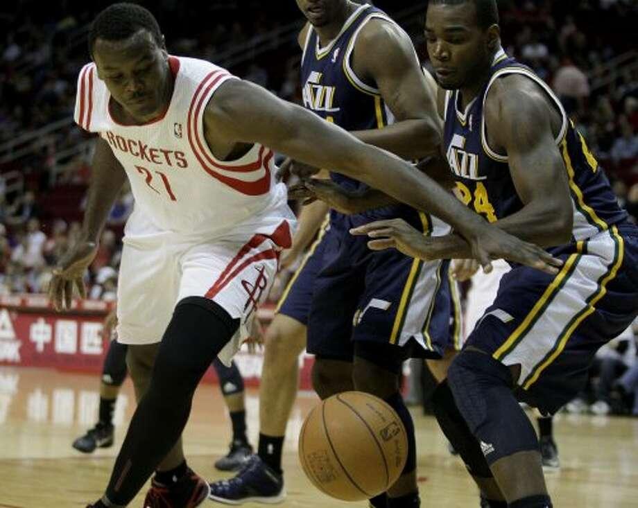 Rockets center Samuel Dalembert (21) beats Utah Jazz power forward Paul Millsap to a loose ball. (Thomas B. Shea / For the Chronicle)