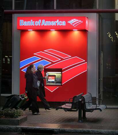 Pedestrians walk past a Bank of America ATM in Charlotte, N.C. near the bank's corporate headquarters on Friday, Jan. 11, 2008. Bank of America Corp. said Friday it has agreed to buy Countrywide Financial for $4 billion in stock, a deal that both rescues the country's biggest mortgage lender and expands the financial services empire of the nation's largest consumer bank. (AP Photo/Nell Redmond) Photo: Nell Redmond, AP