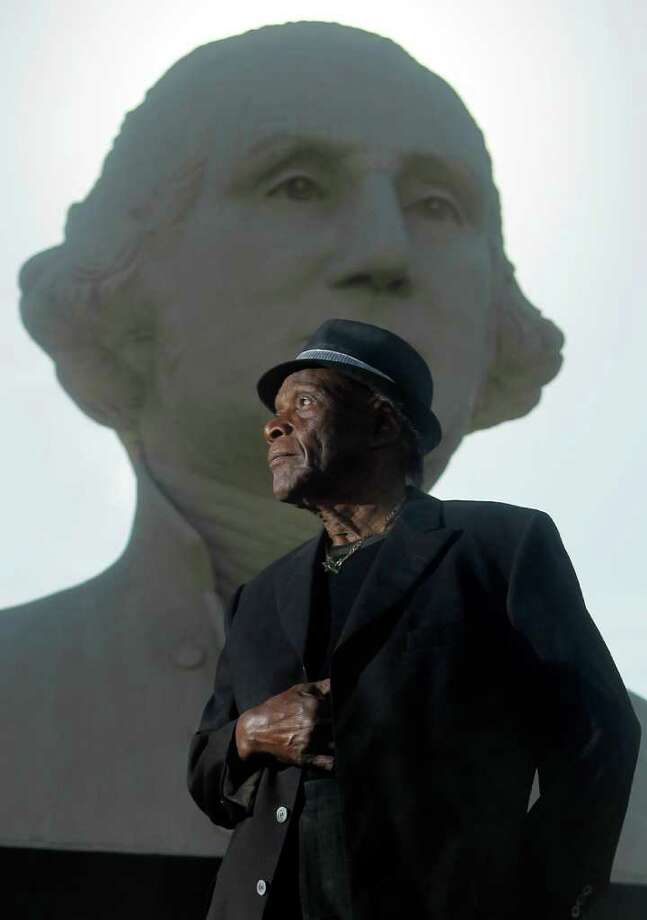 """George Washington in front of Houston artist David Adickes'  sculpture of George Washington.  """"It used to worry me. Now I tell people, 'Hey, I'm on the dollar bill.' It doesn't bother me anymore."""" Photo: Cody Duty / © 2011 Houston Chronicle"""