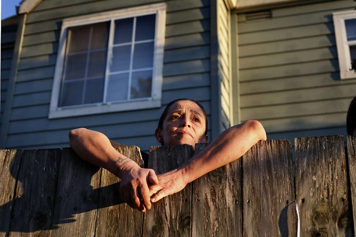 Bobbie, who didn't want to give her last name, looks over her fence along 90th Ave, Wednesday February 15, 2012, where on the sidewalk lies a memorial for a young man who was killed last May in Oakland, Calif.