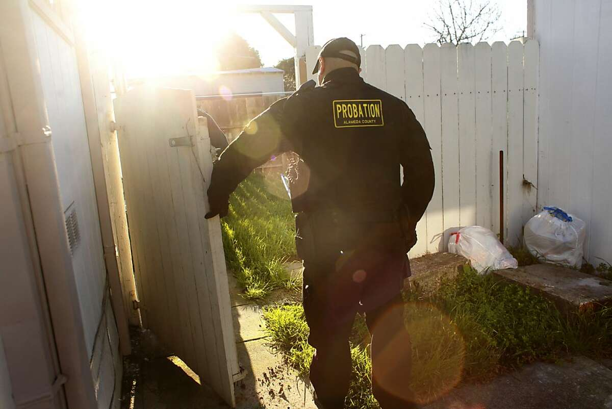 Ray Mizyed of the County Sheriffs Probation Department, search around the homes for guns that were thrown by suspects during a foot chase down Auseon Ave, Wednesday February 15, 2012, in East Oakland, Calif. Mitzyed is working with the Oakland Police Department as part of the 100 block initiative which was created by Mayor Jean Quan to reduce the violence in the areas where 90 percent of the city's homicides and shooting occur.