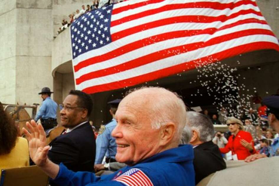 Ohio Sen. John Glenn waves to applauding fans with Mayor Lee Brown during the Veteran's Day parade in downtown Houston Nov. 12, 1998, after his historic shuttle mission. (HOUSTON CHRONICLE)