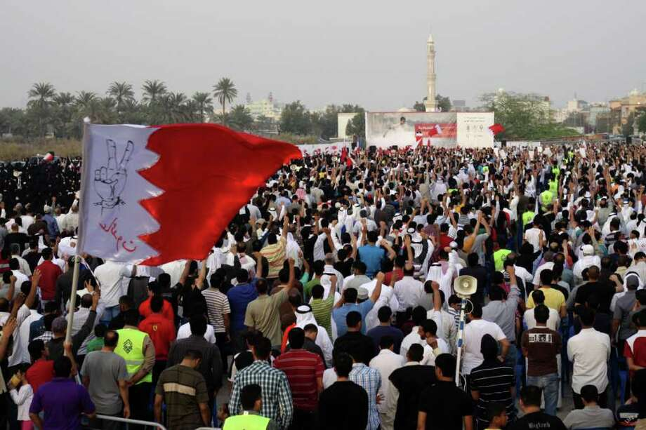 """Thousands of anti-government protesters chant for the freedom of political prisoners Saturday, Feb. 18, 2012, in Manama, Bahrain, during a rally organized by the main political opposition societies. The Bahraini flag in foreground says """"Steadfast"""" on the image and """"We are coming back"""" beneath it, referring to the heavily barricaded area that had been the main site of last spring's pro-democracy uprising. (AP Photo/Hasan Jamali) Photo: Hasan Jamali, Associated Press / AP"""