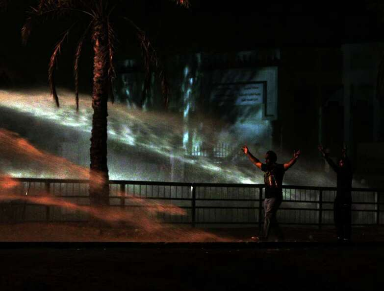 Bahraini anti-government protesters gesture in the spray of police water canons during clashes Frida