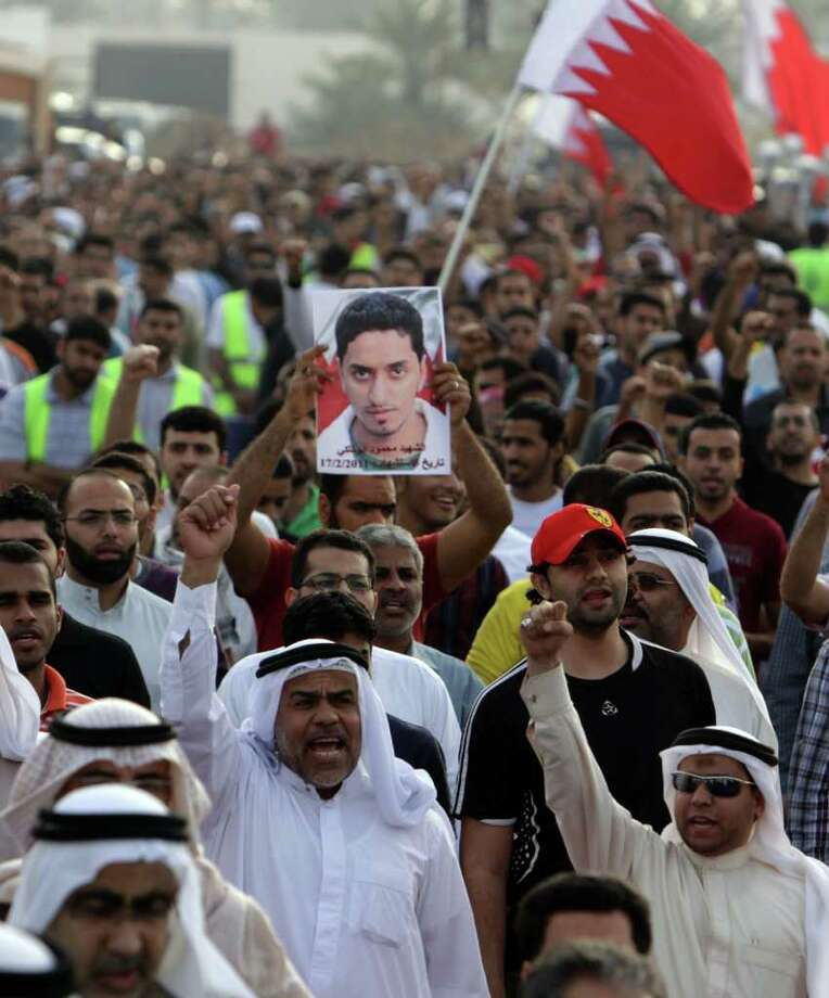 Bahraini protesters chant anti-government slogans, wave Bahraini flags and raise an image of Mahmoud Abu Taki, who died in Bahrain's pro-democracy uprising last year, during a rally Saturday, Feb. 18, 2012, in Manama, Bahrain, by the main political opposition societies. Participants included Abu Taki's parents as well as  relatives of others who have died during the past year of the uprising. (AP Photo/Hasan Jamali) Photo: Hasan Jamali, Associated Press / AP