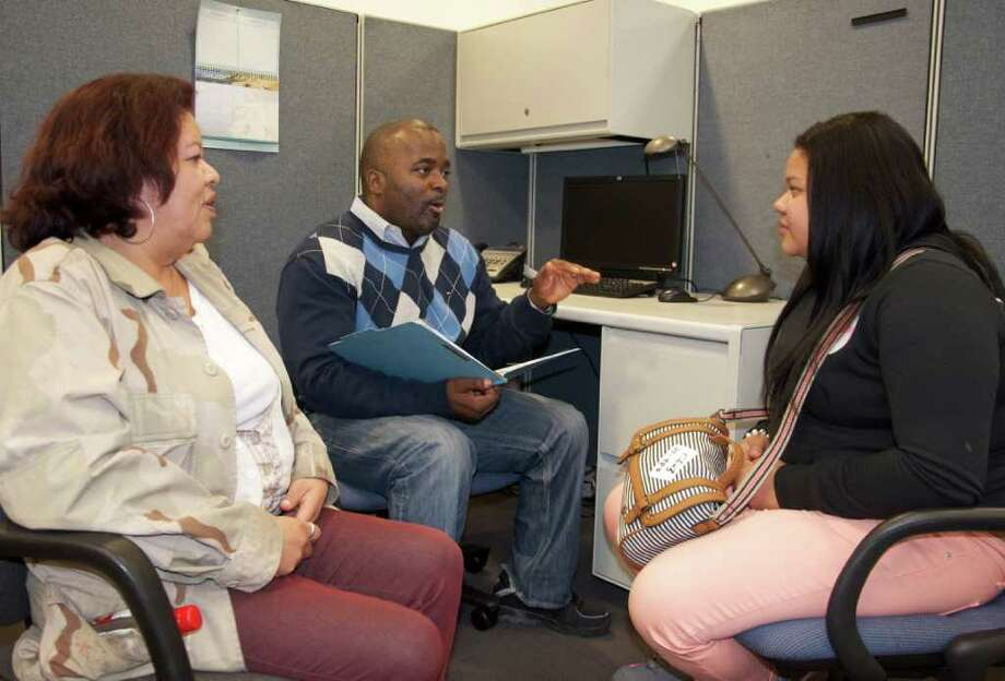 Reggie McNeil, the program manager for case management at the Beacon, talks to a Houston family seeking housing. The Beacon has had to cut back on its case management services as funding has dwindled in recent years. Photo: Pete Holley.