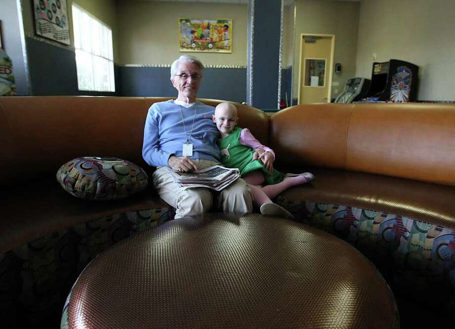 "David Cobb and granddaughter Julia Cobb, 6, spend time together in the sports room at the Ronald McDonald House at 1907 Holcombe. ""Everyone here has been kind and gracious.  We couldn't do this with out them,"" Cobb says. Photo: Karen Warren / © 2012  Houston Chronicle"