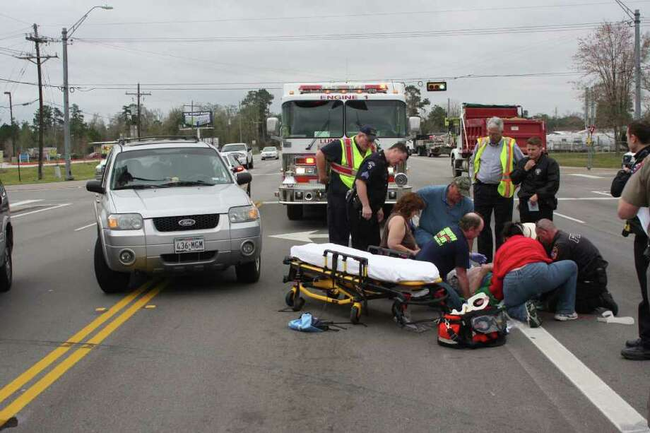 First responders assist a man who was hit by a pickup truck Monday afternoon near Lumberton. Photo: David Lisenby