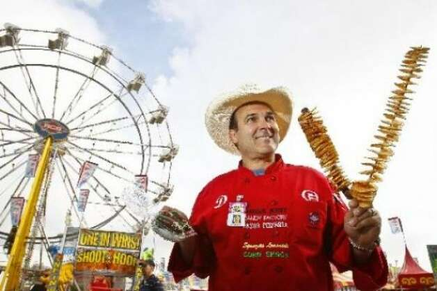 Dominic Palmieri with RCS Carnival Foods holds two Texas Tator Twisters and Chocolate Dipped Jalapenos (Michael Paulsen / chron.com)