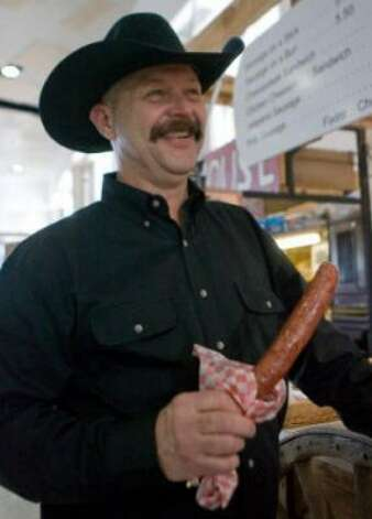 Denny Wagoner of Sheridan, Wyo., enjoys a sausage on a stick from the Burton Sausage booth. (Steve Campbell / chron.com)