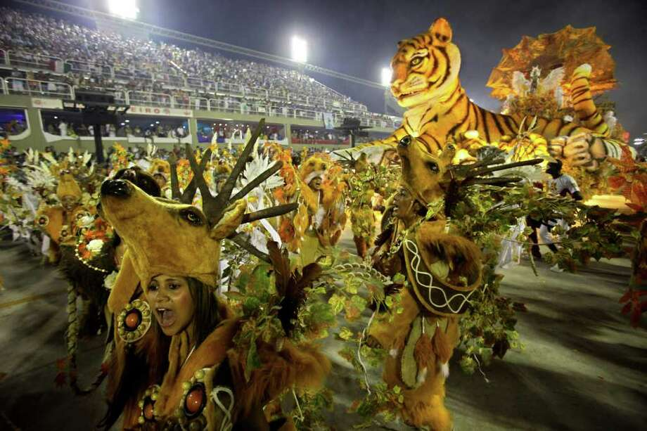 Revelers dance during Porto da Pedra samba school parade at the Sambadrome in Rio de Janeiro, Brazil, Monday, Feb. 20, 2012. Millions watched the sequin-clad samba dancers at Rio de Janeiro's iconic Carnival parade.  (AP Photo/Victor R. Caivano) Photo: Victor R. Caivano, ASSOCIATED PRESS / Associated Press
