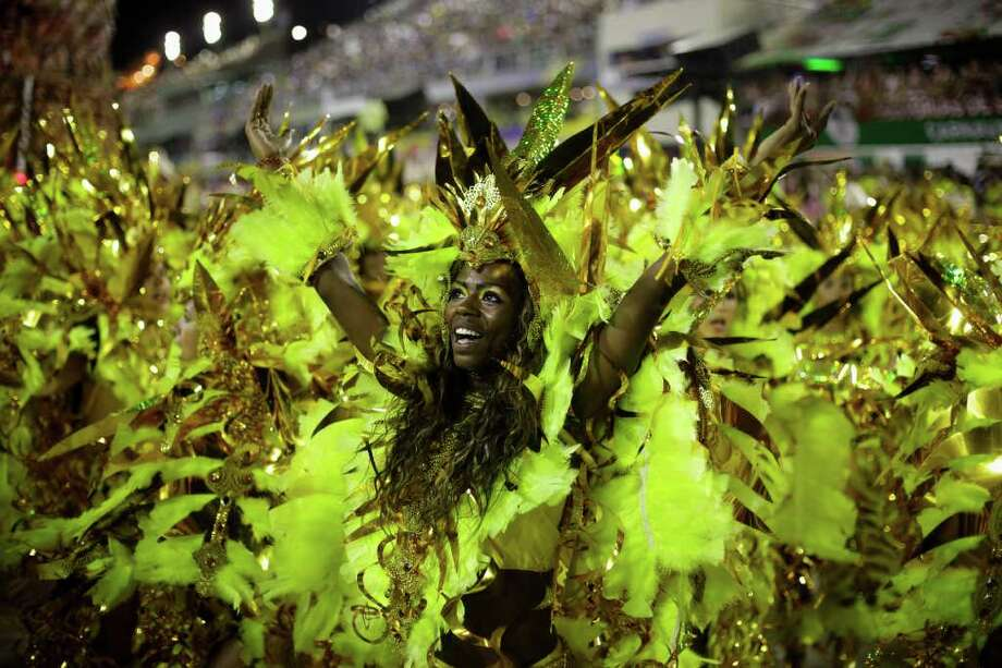 Revelers dance during Beija Flor samba school parade at the Sambadrome in Rio de Janeiro, Brazil, Monday, Feb. 20, 2012. Millions watched the sequin-clad samba dancers at Rio de Janeiro's iconic Carnival parade.  (AP Photo/Victor R. Caivano) Photo: Victor R. Caivano, ASSOCIATED PRESS / Associated Press