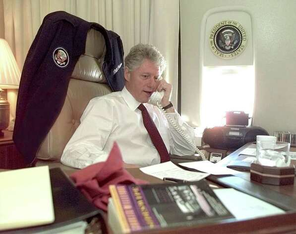 President Bill Clinton talks by phone from his office aboard an unspecified Air Force One on November 2, 1997. Photo: PAUL J. RICHARDS, AFP/Getty Images / AFP