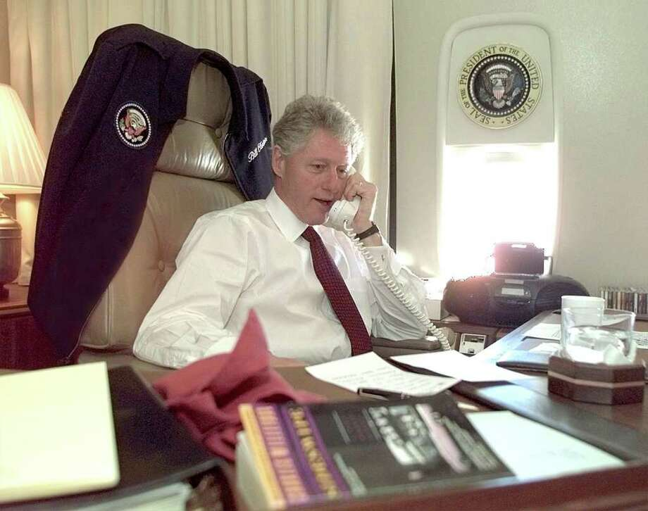 President Bill Clinton talks by phone from his office aboard Air Force One on November 2, 1997. Photo: PAUL J. RICHARDS, AFP/Getty Images / AFP