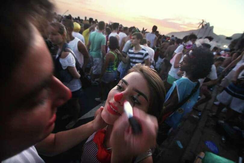RIO DE JANEIRO, BRAZIL - FEBRUARY 18: A man paints a woman's face during Carnival celebrations along