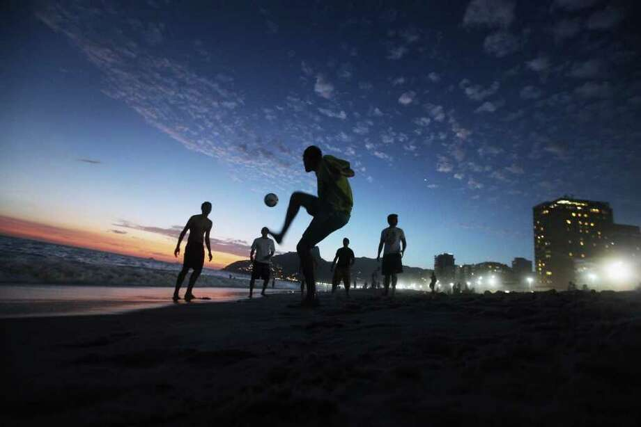 RIO DE JANEIRO, BRAZIL - FEBRUARY 18:  Brazilian revelers play soccer at sunset during Carnival celebrations along Ipanema beach on February 18, 2012 in Rio de Janiero, Brazil. Carnival is the grandest holiday in Brazil, annually drawing millions in raucous celebrations culminating on Fat Tuesday before the start of the Catholic season of Lent which begins on Ash Wednesday. Police strikes in Salvador and Rio de Janiero in recent weeks threatened Carnival and raised questions about the country?s preparedness to host the upcoming 2014 World Cup and 2016 Summer Olympics.   (Photo by Mario Tama/Getty Images) Photo: Mario Tama, Getty Images / 2012 Getty Images