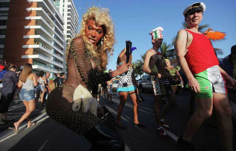 RIO DE JANEIRO, BRAZIL - FEBRUARY 18:  Brazilian revelers parade during Carnival celebrations along Ipanema beach on February 18, 2012 in Rio de Janiero, Brazil. Carnival is the grandest holiday in Brazil, annually drawing millions in raucous celebrations culminating on Fat Tuesday before the start of the Catholic season of Lent which begins on Ash Wednesday. Police strikes in Salvador and Rio de Janiero in recent weeks threatened Carnival and raised questions about the country?s preparedness to host the upcoming 2014 World Cup and 2016 Summer Olympics.   (Photo by Mario Tama/Getty Images) Photo: Mario Tama, Getty Images / 2012 Getty Images