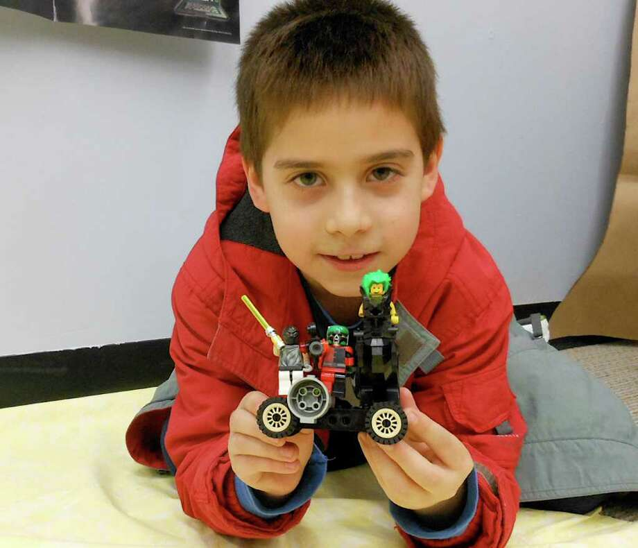 Jonathan Unger, 8, shows off a Star Wars-themed Lego creation he made Friday at the Fairfield Woods Branch Library. Photo: Mike Lauterborn / Fairfield Citizen contributed