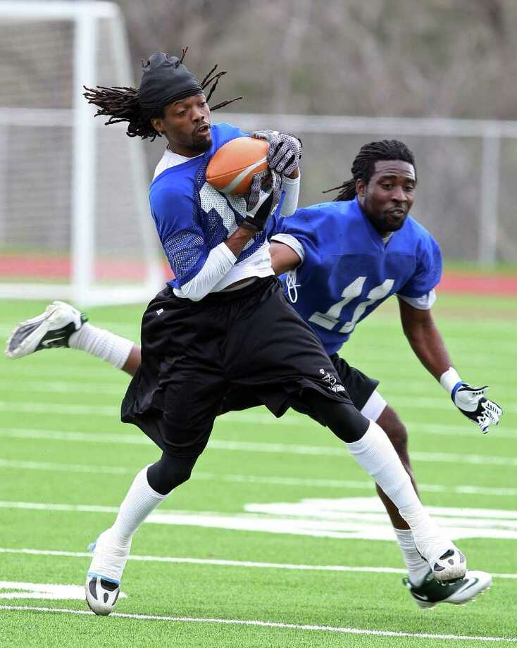 San Antonio Talons wide receiver Brent Holmes catches the football under pressure from defensive back Maurice Holmes as the team goes through their first practice at Wheatley Heights Sports Complex, Monday, Feb. 20, 2012. The Arena Football League team will have a scrimmage against the San Jose SaberCats on Feb. 29th at the Alamodome. The season starts on March 10th against the Utah Blaze.  JERRY LARA/glara@express-news.net Photo: Jerry Lara, San Antonio Express-News / © 2012 San Antonio Express-News