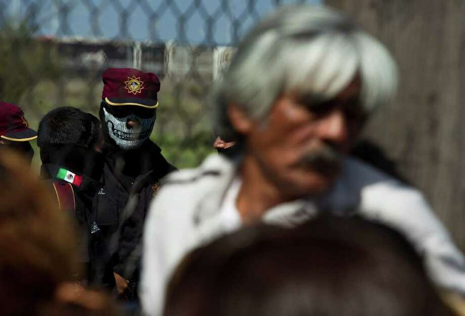 A state police officer wearing a face mask stands behind the fence as relatives of inmates wait for news after a prison riot at Apodaca correctional state facility in Apodaca on the outskirts of Monterrey, Mexico, Sunday Feb. 19, 2012.  A fight among inmates at the prison led to a riot that killed dozens on Sunday, according to a security official. Photo: AP
