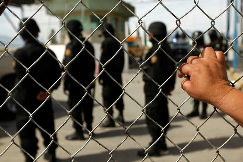 "A relative of an inmate observes policemen behind the security fence after a riot inside Apodaca prison, on February 20, 2012, near Monterrey, state of Nuevo Leon, Mexico. At least 44 inmates have been killed during a riot Sunday and about 30 alleged members of the drug cartel ""Los Zetas"" were rushed out from the prison. AFP PHOTO/Julio Cesar Aguilar (Photo credit should read Julio Cesar Aguilar/AFP/Getty Images) Photo: JULIO CESAR AGUILAR / AFP"